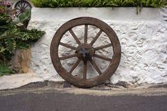 Uma roda quebrada de madeira antiga está perto da parede whitewashed com plantas fotografia de stock