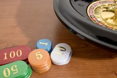 Uma roleta e um casino colorido lascam-se em uma tabela de madeira fotografia de stock