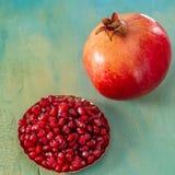Uma romã e umas grões vermelhas do fruto em uma placa imagem de stock