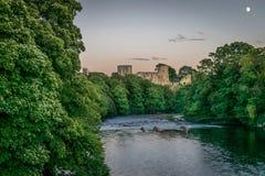 Uma ruína de um castelo que projeta-se através de uma floresta ao lado de um rio com uma lua imagens de stock royalty free
