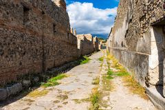 Uma rua cobbled antiga nas ruínas de Pompeii Cidade romana destruída pelo vulcão do Vesúvio fotos de stock royalty free