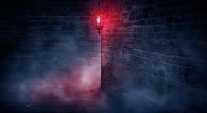 Uma rua escura, uma lanterna vermelha, uma parede de tijolo, fumo, um canto da construção, uma lanterna que brilha imagens de stock
