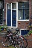 Uma rua pequena em Amsterdão e bicicletas perto da casa Imagens de Stock