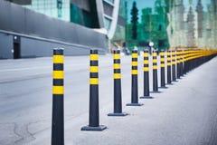 Uma série de cargos cinzentos e amarelos listrados do sinal em uma estrada asfaltada fotografia de stock