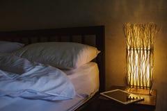 Uma sala acolhedor com uma cama e uma tabuleta Trabalho em casa em circunstâncias confortáveis Imagem de Stock Royalty Free