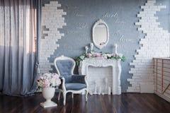Uma sala cinzenta com uma chaminé branca e uma cadeira cinzenta do vintage, decoradas toda com peônias e as flores bonitas; fotografia de stock royalty free