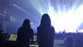 Uma sala de concertos aglomerada com luzes da fase da cena, desempenho da mostra da rocha, com silhueta dos povos vídeos de arquivo