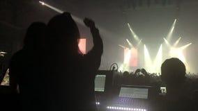 Uma sala de concertos aglomerada com luzes da fase da cena, desempenho da mostra da rocha, com silhueta dos povos video estoque