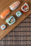 Uma seleção de rolos de sushi dos peixes frescos na placa de bambu Fotos de Stock Royalty Free