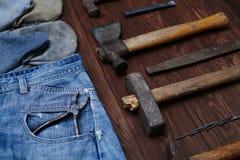Uma seleção de calças de brim vestidas carpinteiro do jogo e da sarja de Nimes de ferramentas com glo Imagens de Stock