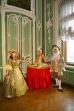 Uma senhora-bebida, uma tabela da menina, tabela e atores vivos e animadores nos trajes do período dos rococós Imagens de Stock