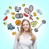 Uma senhora bonita que esteja tentando fazer uma escolha em favor de alguma atividade do esporte Os ícones coloridos do esporte s Fotografia de Stock