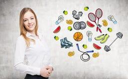 Uma senhora bonita que esteja tentando fazer uma escolha em favor de alguma atividade do esporte Os ícones coloridos do esporte s Imagens de Stock Royalty Free