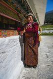 Uma senhora butanesa feliz que rola as rodas de oração, stupa de Chorten Kora, distrito de Trashiyangtse, Butão oriental imagem de stock royalty free