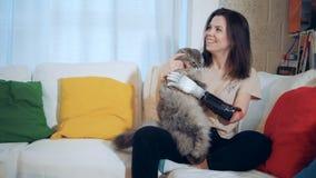 Uma senhora com um braço artificial está jogando com seu gato vídeos de arquivo
