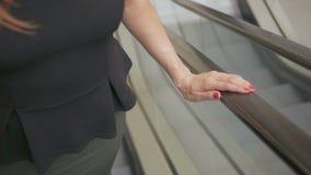 Uma senhora do negócio está montando uma escada rolante Close-up de uma mão que sustenta uns trilhos vídeos de arquivo