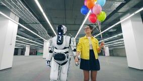 Uma senhora e um robô estão andando ao longo do salão junto video estoque