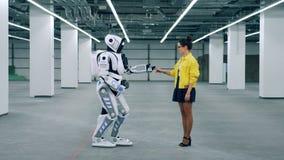 Uma senhora está dando sua mão a um robô alto vídeos de arquivo