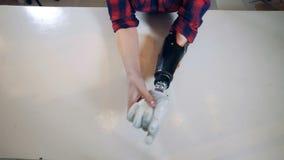 Uma senhora está montando um braço protético com sua mão saudável filme