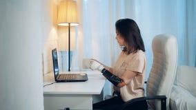 Uma senhora está trabalhando em um portátil com seus mão e café robóticos das bebidas