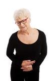 Uma senhora idosa está tendo uma dor de estômago. Fotografia de Stock Royalty Free