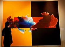 Uma senhora na frente de uma pintura abstrata do museu Foto de Stock