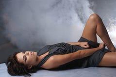 Uma senhora nova e 'sexy' em um fundo fumarento Fotografia de Stock Royalty Free