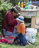 Uma senhora peruana e seu filho em uma tenda da bebida ao lado das ruínas do Inca do Moray no Peru Imagens de Stock