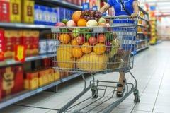 Uma senhora que empurra um carrinho de compras na compra da alameda Imagens de Stock