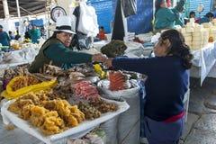 Uma senhora serve um cliente no mercado em Cusco central, Peru Imagens de Stock Royalty Free