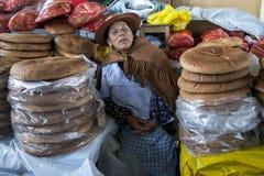 Uma senhora toma uma sesta rápida em sua tenda do pão em um mercado em Cusco no Peru Fotos de Stock