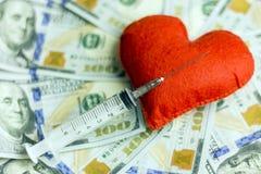 Uma seringa descartável médica encontra-se em um coração vermelho contra um fundo de notas de dólar dos E.U. O conceito de vender Imagens de Stock