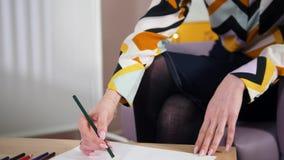 Uma sessão no paciente da jovem mulher do psicólogo A que tira no papel com lápis da cor video estoque