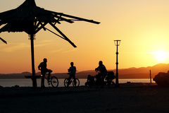 Uma silhueta caçoa com as bicicletas na praia durante o por do sol Imagem de Stock