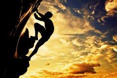 Uma silhueta da escalada livre do homem na montanha Fotos de Stock Royalty Free