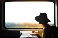 Uma silhueta da mulher asiática do moderno bonito que viaja no trem fotos de stock