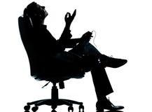 Uma silhueta de escuta da música do homem de negócio Imagens de Stock