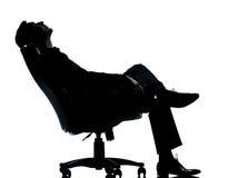 Uma silhueta de relaxamento de assento do homem de negócio Imagens de Stock Royalty Free