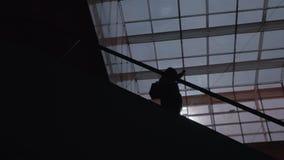 Uma silhueta de um homem que move-se para baixo em uma escada rolante video estoque