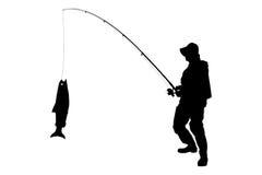 Uma silhueta de um pescador com um peixe Fotos de Stock