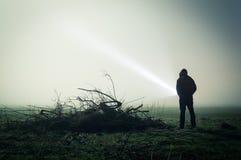 Uma silhueta delével de uma figura encapuçado solitária em um campo em uma noite nevoenta com uma tocha Com uma obscuridade edite foto de stock royalty free