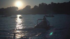 Uma silhueta do barco de motor no por do sol vídeos de arquivo