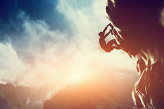 Uma silhueta do homem que escala na rocha, montanha Imagens de Stock