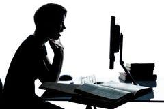 Uma silhueta nova da menina do menino do adolescente que estuda com computador c Foto de Stock Royalty Free