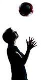 Uma silhueta nova da menina do menino do adolescente que lanç o futebol do futebol Foto de Stock