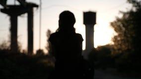 Uma silhueta unfocused de uma jovem mulher, andando afastado no por do sol filme