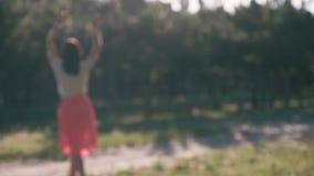 Uma silhueta unfocused de uma mulher bonita nova, que ponha suas mãos atrás de sua cabeça video estoque