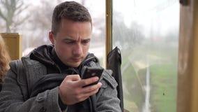 Uma situação do homem novo em um bonde e utilização de seu telefone video estoque
