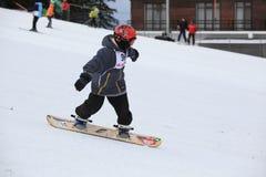 Uma snowboarding da criança em uma inclinação de montanha Fotos de Stock Royalty Free