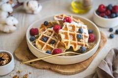 Uma sobremesa doce do waffle decorada com bagas e porcas em uma molho-bandeja bonita em uma toalha de mesa da lona Luz natural imagem de stock